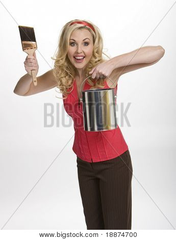 Three quarter view of pretty woman standing, enthusiastically holding paintbrush and paint can, on white background.