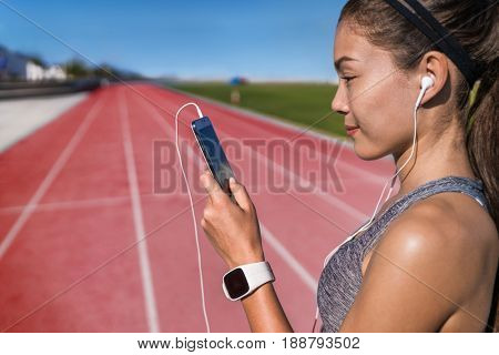 poster of Runner listening to smart phone music app on red running tracks. Asian woman athlete with earphones