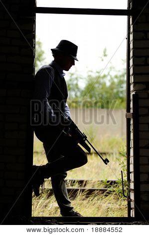 silhueta de jovem gangster com rifle
