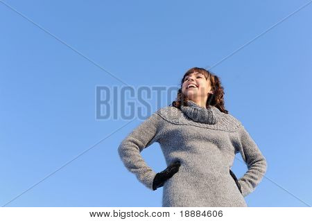 full of life smiling girl in grey sweater isolated in blue sky