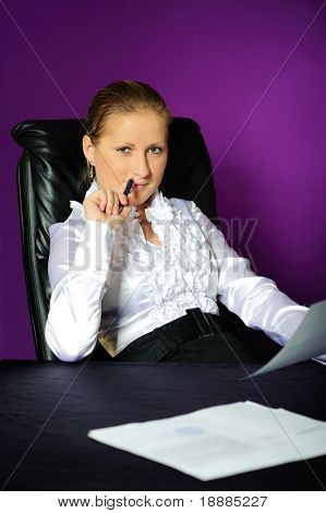 assured business woman sit in big black armchair, isolated on violet background