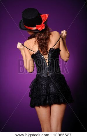 woman with beauty back in black corset posing against violet background. may be use for bdsm and cruel concept