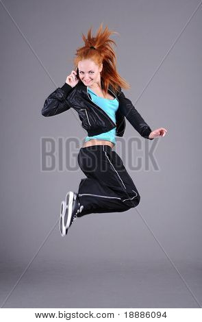 funky young woman jumping and talking phone, isolated on grey background