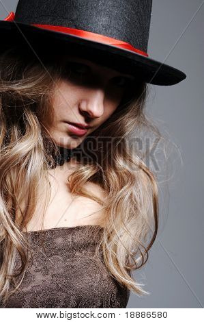 beauty enigmatic woman in black top hat isolated on grey
