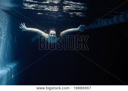 Woman in summer dress swimming under water in the pool