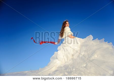 beauty teenager posing in white wedding dress with train