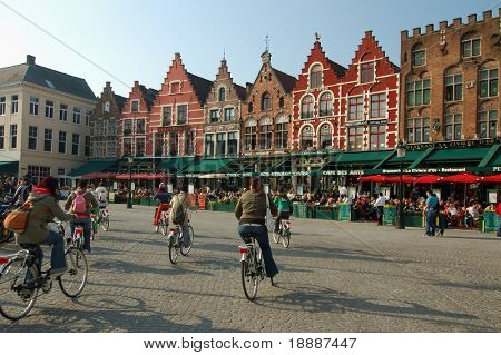 Row of vivid color houses at the paved square of the oldest town in europe brugge and cyclists drivindg on the square