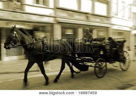 Horse carriage driving through the narrow streets of the oldest european town in motion