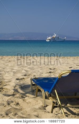 Lonely deck chair with a view over a blue lagoon and a yacht