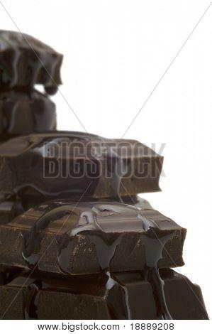 liquid and black bitter chocolate on white background