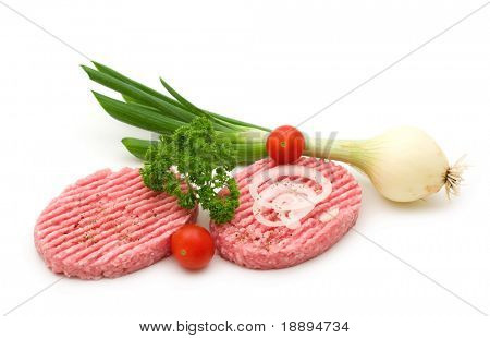 two raw minced beef steak and vegetables