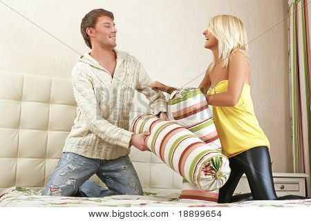 young man and woman withing with pillows on bed