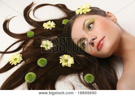 bella joven acostado aislado fondo blanco con flores y pelo que fluye