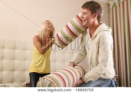young man and woman fighting with pillows on bed
