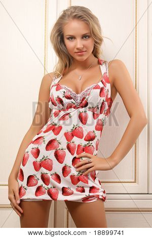 sexy young woman posing  near closet in attractive dress