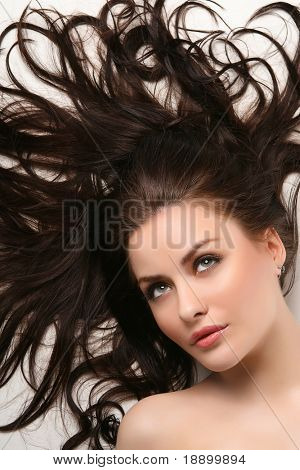 young adult lying on white background with beautiful hair all over
