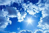 Beautiful blue sky with bright sun and fluffy clouds poster
