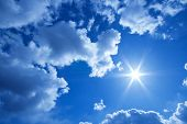 Blue sky with fluffy clouds and bright sun poster