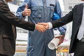 Businessmen Handshake With Engineer Thumbs Up poster