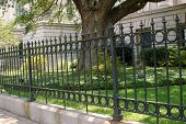 picture of wrought iron  - This classic wrought iron fence surrounds a government building - JPG