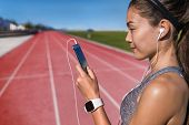 Runner listening to smart phone music app on red running tracks. Asian woman athlete with earphones  poster