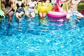 Group of diverse friends enjoying summer time by the pool with inflatable tubes poster