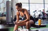 Young woman athlete using cell phone at gym. Latin woman in sportswear checking phone while resting  poster