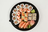 Set of assorted sushi kept in a round black box against white background poster