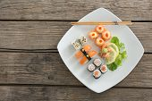 Set of assorted sushi served on tray against wooden background poster