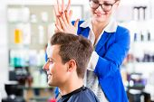 Female coiffeur cutting men hair in hairdresser shop poster