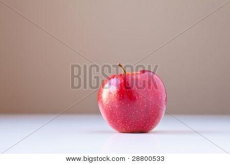 roten Apfel auf weiß mit braunen Hintergrund