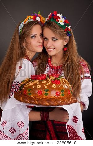 Young Women In Ukrainian Clothes, With Garland And Round Loaf On Black Background