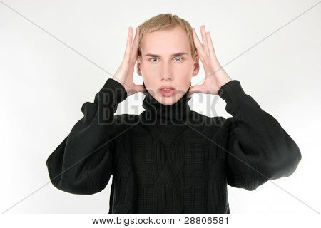 young man with hands next to head over white