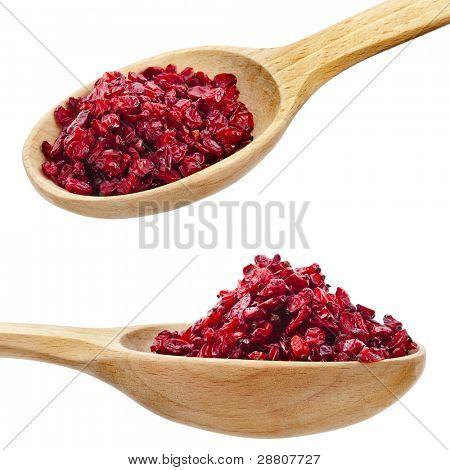 dry red barberry spices on spoons isolated on a white background