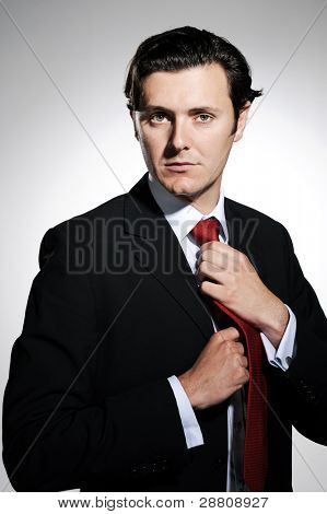 Proud businessman adjusting his appearance before entering a meeting