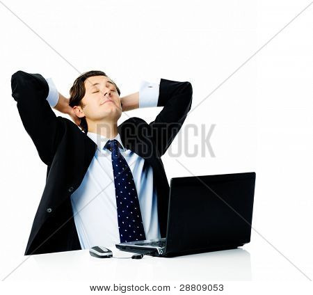 Attractive businessman leans his head back into his hands and closes his eyes, daydreaming about his holiday