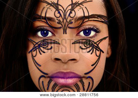 Close Up Beautiful Black Woman with Plastic Henna Art on Face and purple contact lenses.