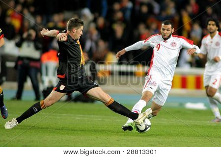 BARCELONA - DEC 30: Tunisian player Yassine Chikhaoui(R) vies with Fontas(L) of Catalonia during the friendly match between Catalonia and Tunisia at Olympic Stadium in Barcelona, Spain on Dec.30, 2011