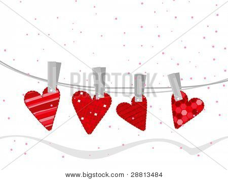 Red color handmade clothes in heart shapes hanging on line white background for Valentine Day and other occasions.