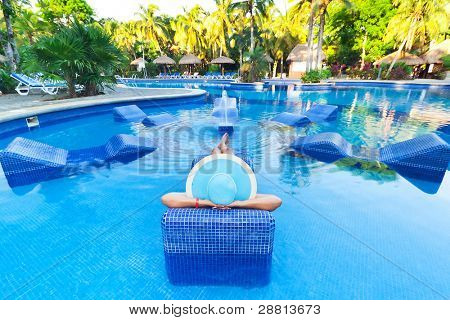 Woman in hat tanning on bed at swimming pool