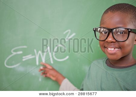 Smart schoolboy showing the mass-energy equivalence on a blackboard