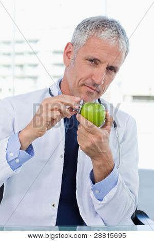 Portrait of a doctor putting his stethoscope on an apple in his office