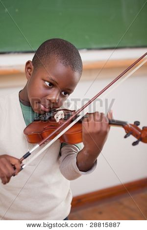 Portrait of a schoolboy playing the violin in a classroom
