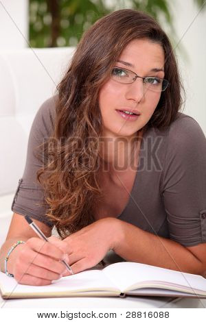 Intelligent young woman writing in a hardback notebook