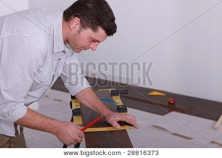 Man laying a floor and measuring a piece of wood