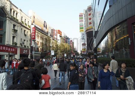 SHANGHAI, CHINA - NOVEMBER 27: Tourists and shoppers crowd the famous Nanjing Street shopping district on November 27, 2011 in Shanghai, China. Shanghai is a financial powerhouse in modern China.