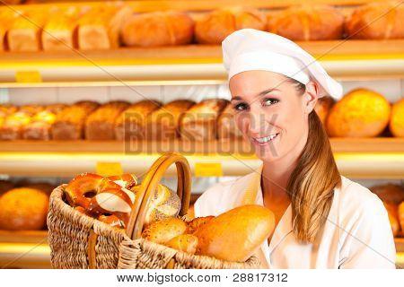 Female Baker oder Verkäuferin in ihre Bäckerei verkauft frisches Brot, Gebäck und Bäckerei Produkte im Warenkorb