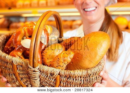 Female baker or saleswoman in her bakery selling fresh bread, pastries and bakery products in basket