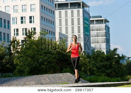 Urban sports - young woman jogging for fitness in the city on a beautiful summer day