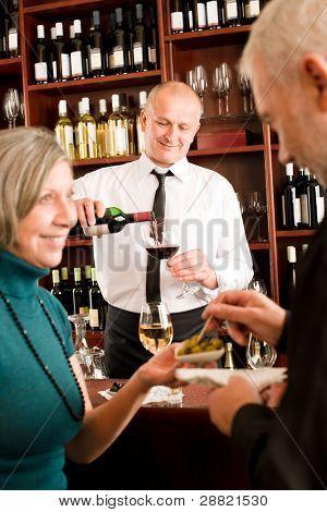 Wine bar senior couple enjoy drink smiling barman pour glass